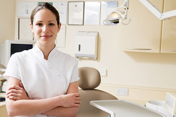 a smiling dental assistant standing in a dental exam room