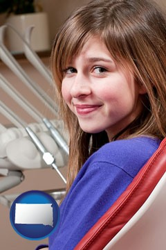 a smiling dental clinic patient - with South Dakota icon